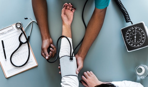 An arm in a blood pressure cuff and a medical chart