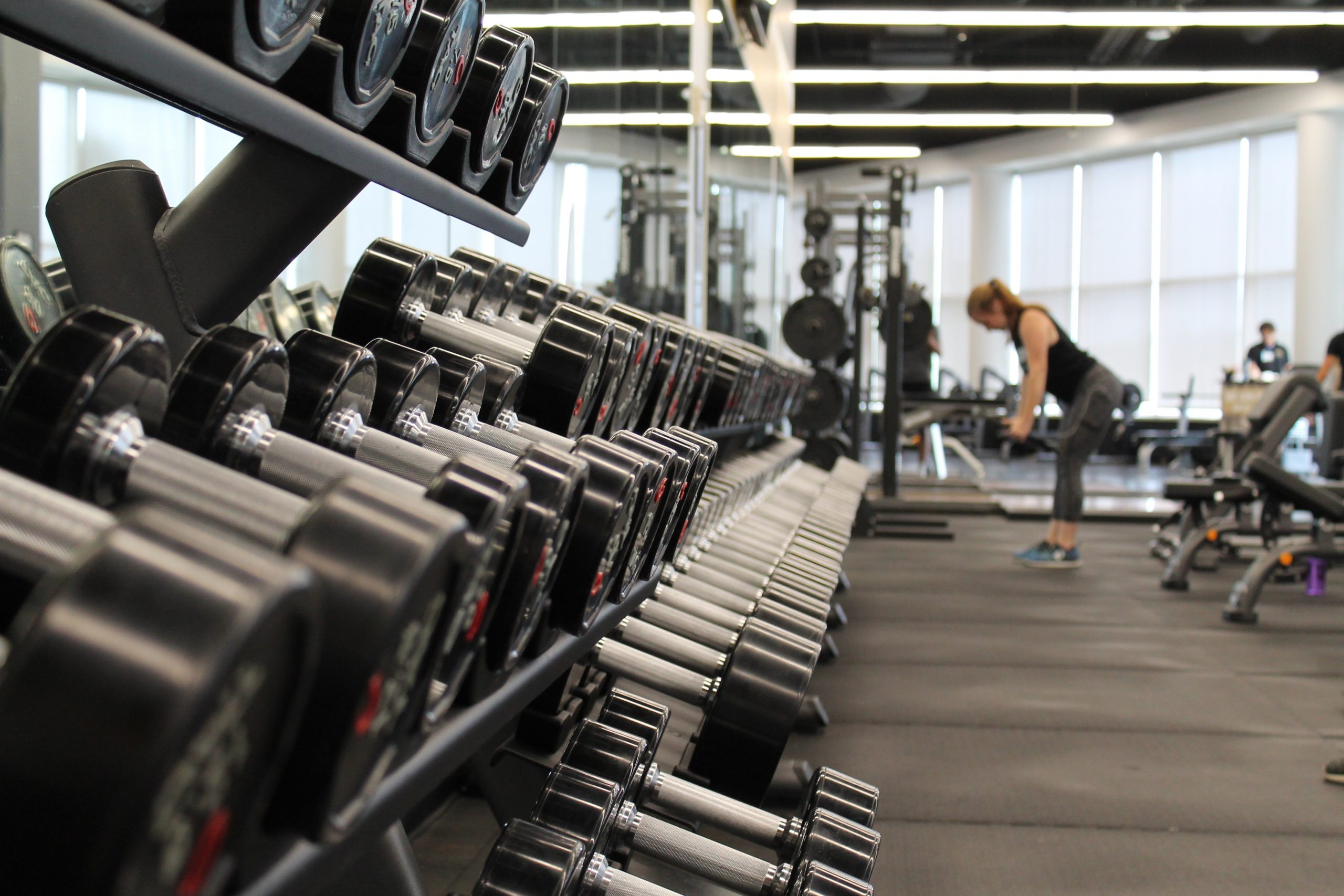 Room with rows of dumbbells with a woman lifting weights in the distance.
