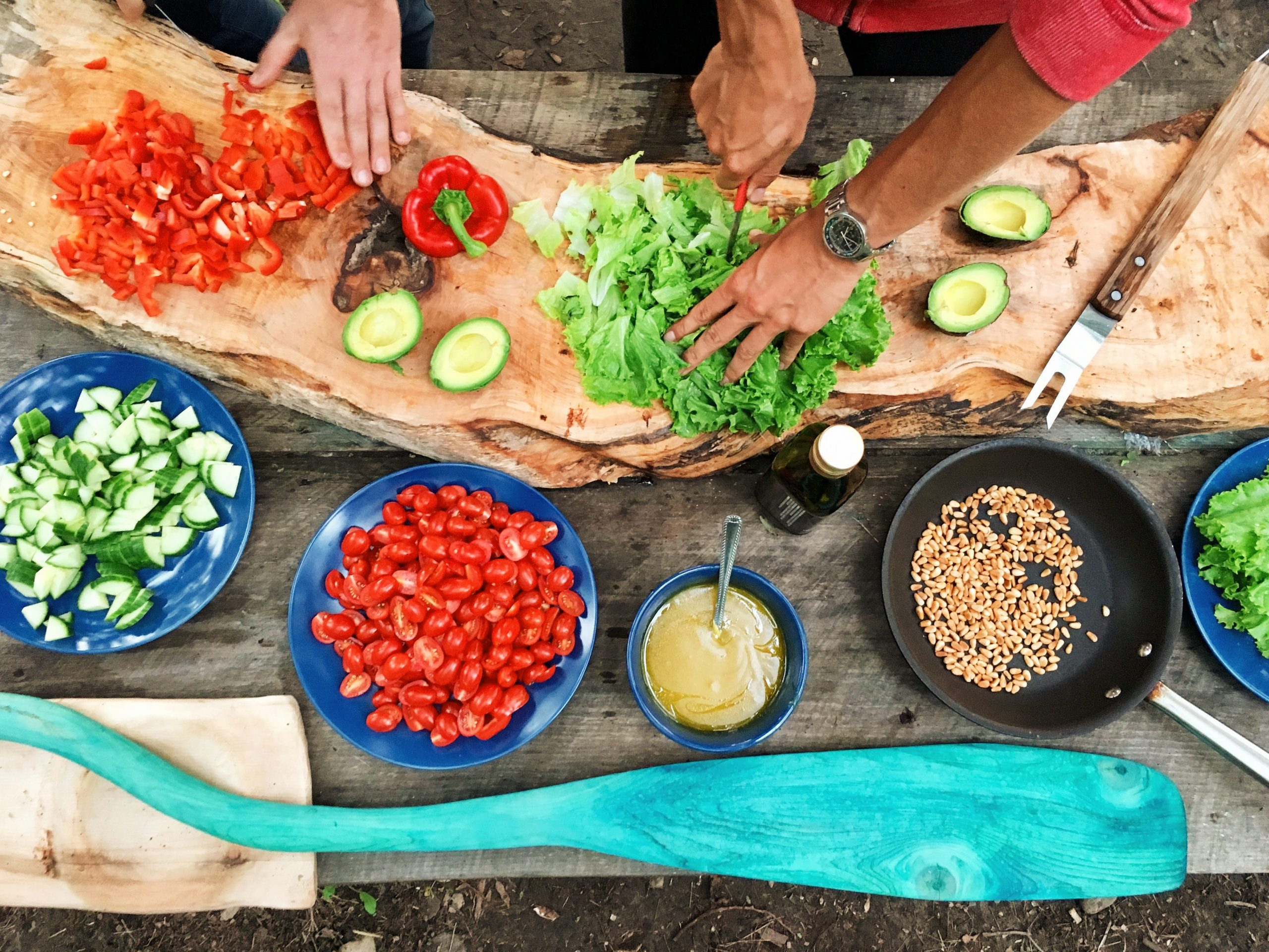 A variety of colorful fresh food being chopped and prepared for a salad (lettuce, tomatoes, red peppers).