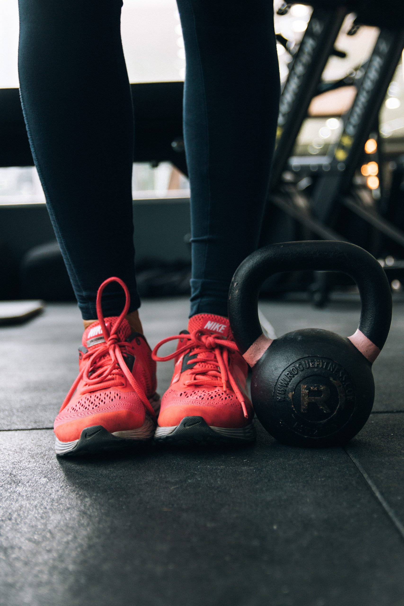 Legs and feet in red tennis shoes with a kettlebell sitting next to them.