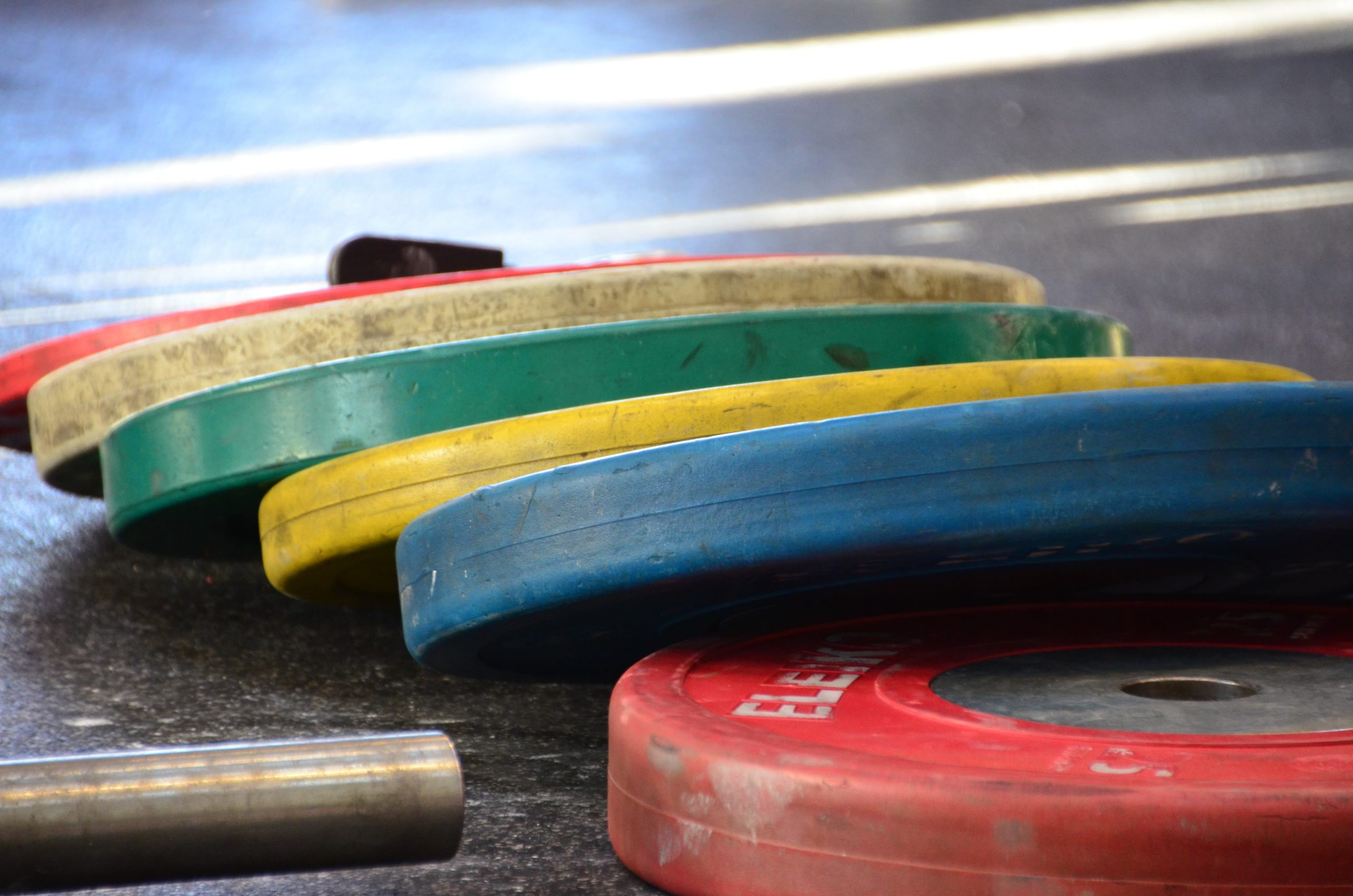 Colorful weight discs laying on the ground.